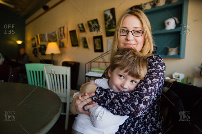Woman hugs her son in a cafe