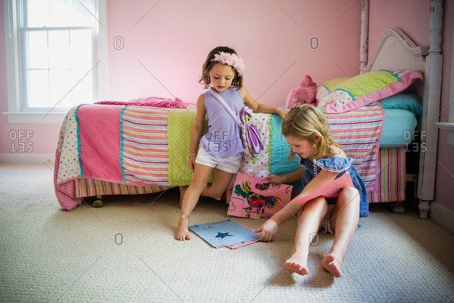 Two young girls look at drawings in bedroom