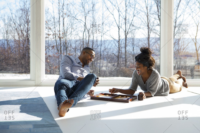 A couple plays backgammon on their living room floor