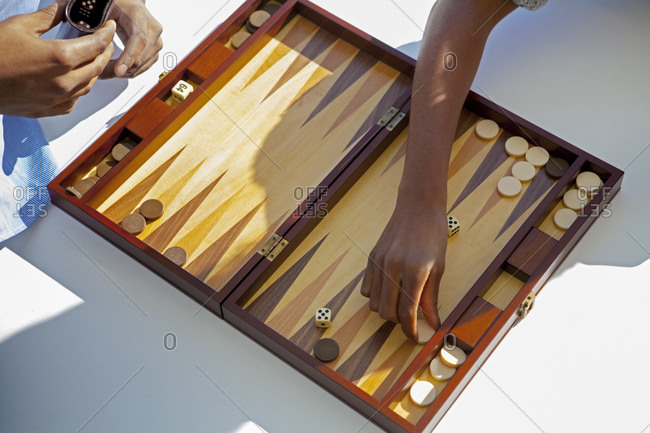 A couple plays a game of backgammon on their living room floor