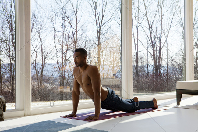 A young man practices yoga in his living room