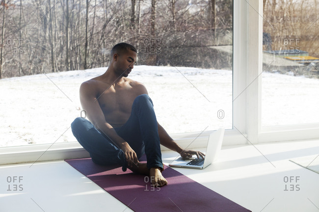 A man checks his laptop on his yoga mat