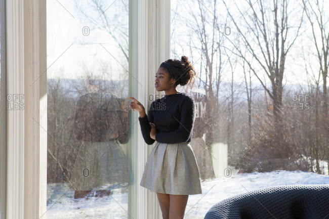 A young woman points out of the window of her living room