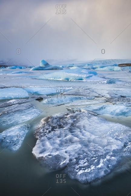 Frozen icebergs locked in the frozen waters of Fjallsarlon Glacier lagoon, South East Iceland, Iceland