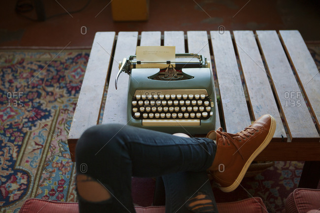 A woman with legs crossed sitting at a typewriter