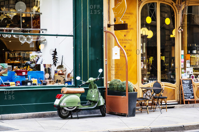 A motorcycle parked outside of a Parisian storefront