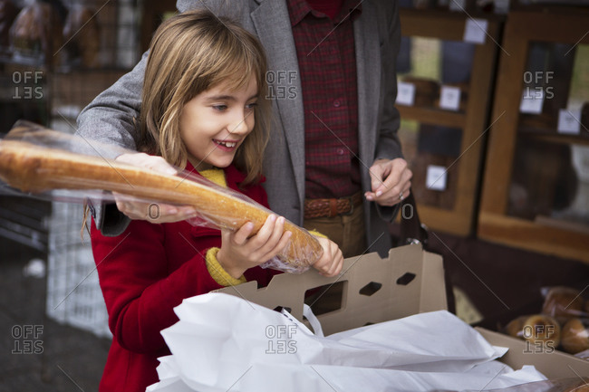 A grandmother and granddaughter buy a baguette at an open air market