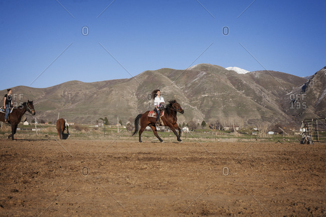 Two young women ride horses in a pen