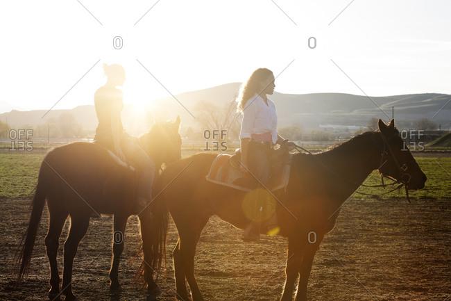 Two girls on horseback in the sunlight