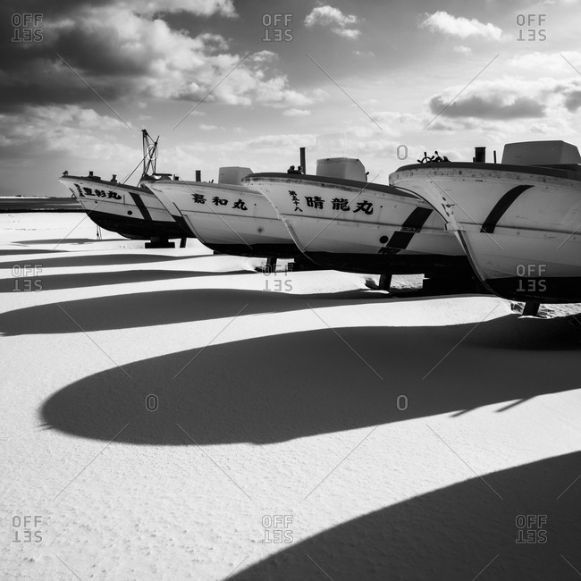 Hokkaido, Japan - January 13, 2015: Fishing boats casting long shadows on the snow