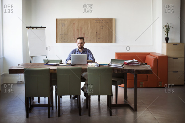 Man working at a rustic table in a stylish office