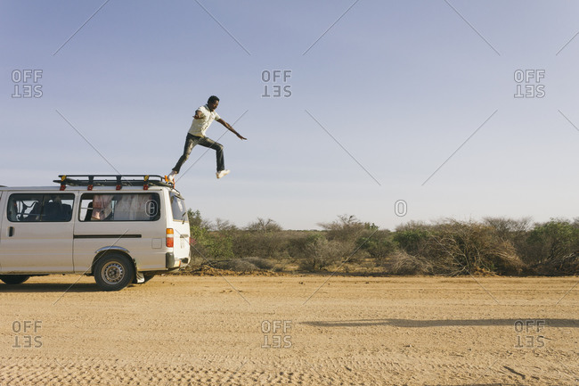 Man jumping from the roof of a van on a dirt road in african savanna, Ethiopia