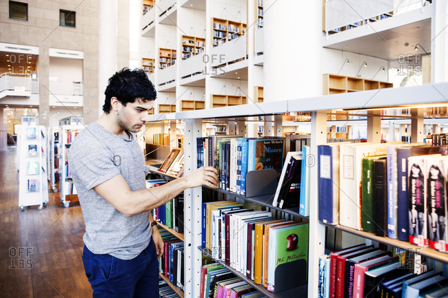 Young man searching for books in a library