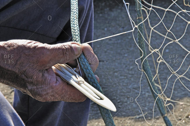 An old man fixes a fishing net