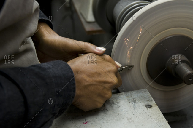 A worker sharpens a pair of pliers