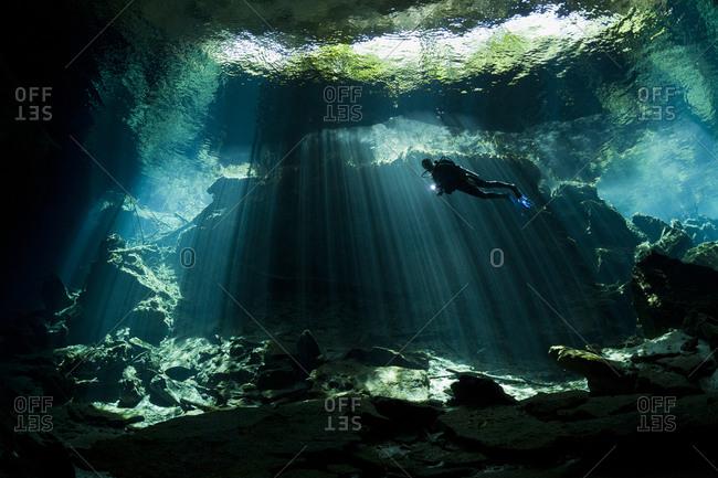 Scuba diver exploring in cenote, Yucatan Peninsula, Mexico
