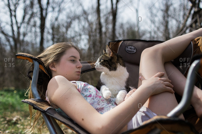 Teenage girl relaxing outdoors in a chair with pet cat on her stomach
