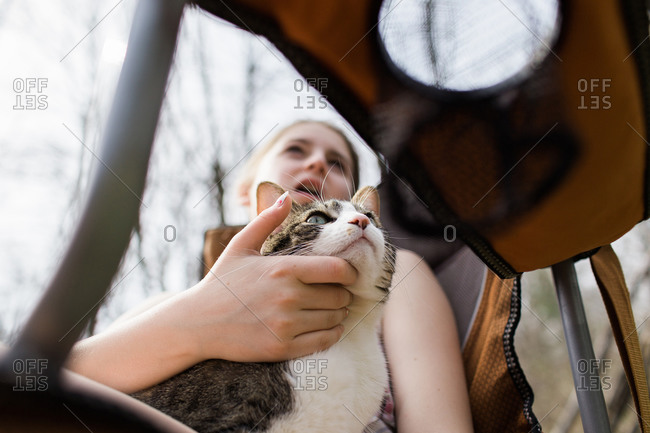 Teen girl in a camp chair scratches her cat\'s chin