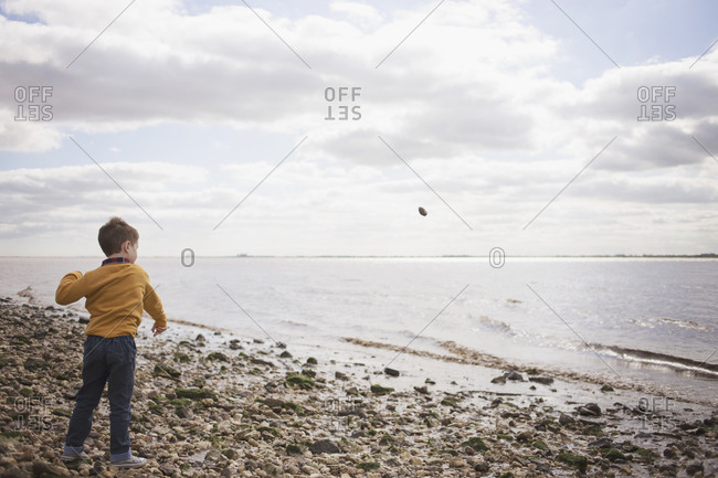 Boy throws rock into the water at the beach