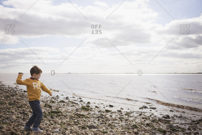 Boy throws a rock at the beach