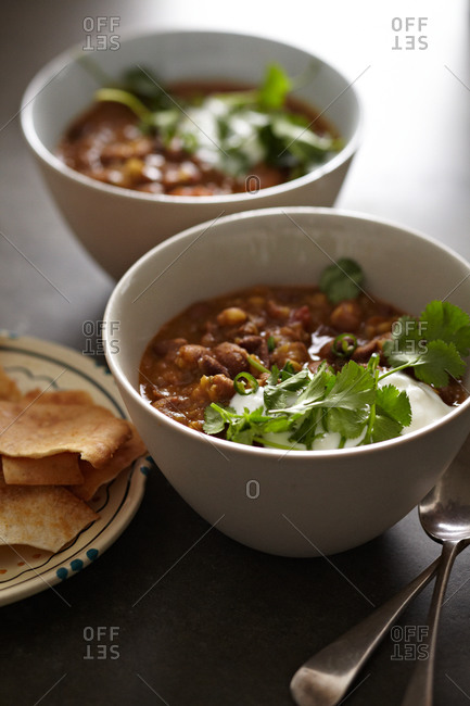 Two bowls of pinto beans served with tortilla chips