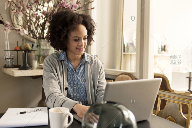 Busy woman working at laptop from her dining table