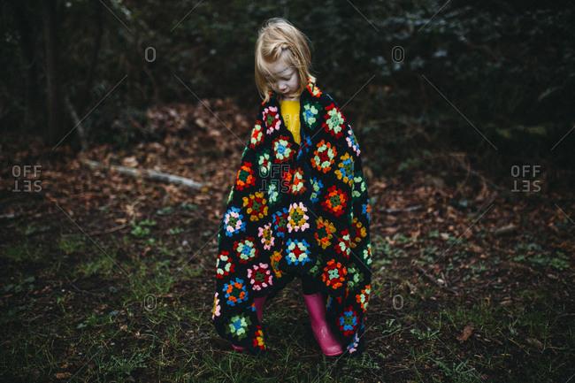 Girl wrapped in crocheted blanket standing outside