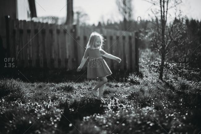 Girl frolicking in backyard