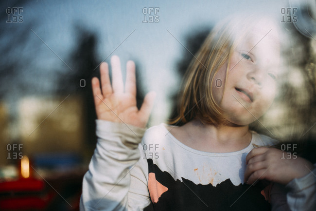 Portrait of girl at window waving goodbye