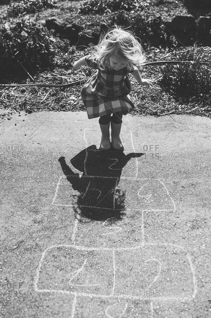 Young girl playing hopscotch alone