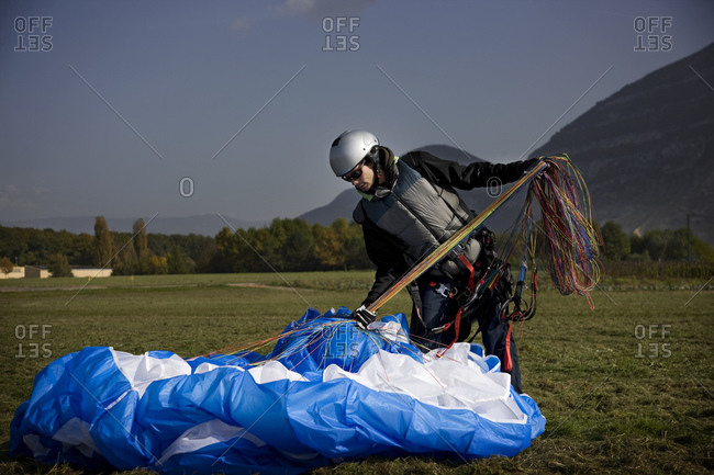 A paraglide packs his glide after a ride off of Geneva, Switzerland's Mount Saleve