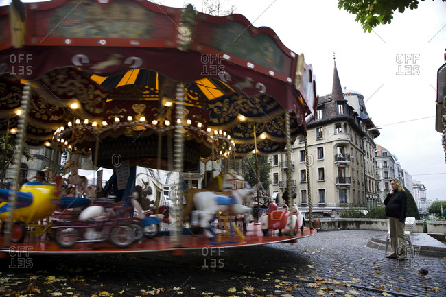 A pregnant woman watches a carousel going around on a quiet rainy morning in Geneva, Switzerland