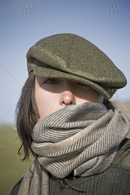 A woman wearing a wool cap and scarf on the 18th hole of a Scottish golf course