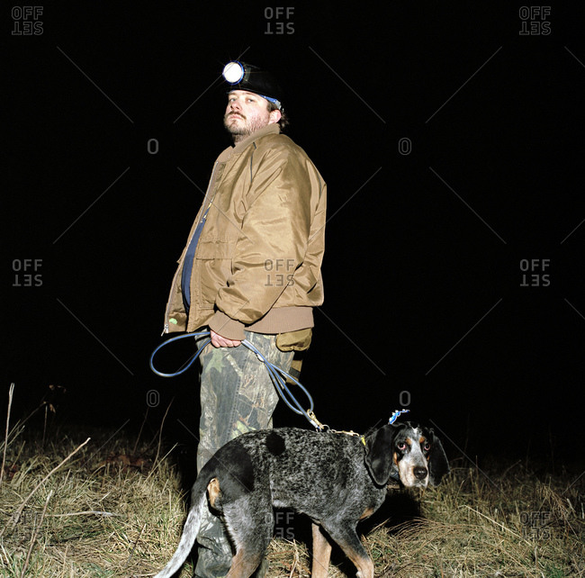 """A hunter with his """"coon dog"""" walking in a field"""