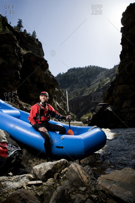A river rafting guide, sitting in a raft while holding a paddle on the side of a river outside of Boulder, Colorado