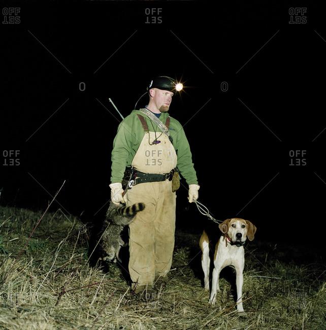 A hunter holding a dead raccoon