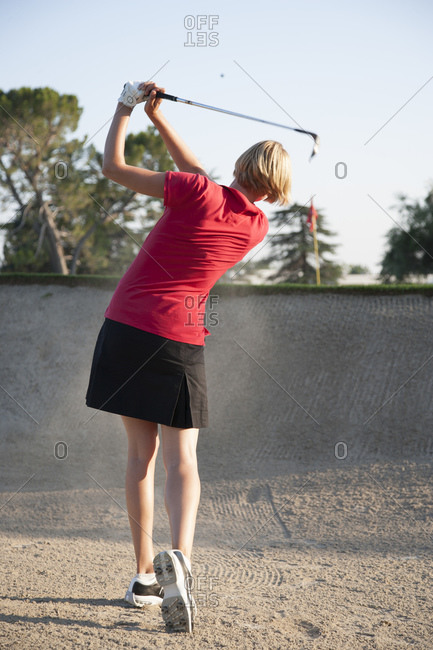 A woman playing golf swings her way out of a sand trap