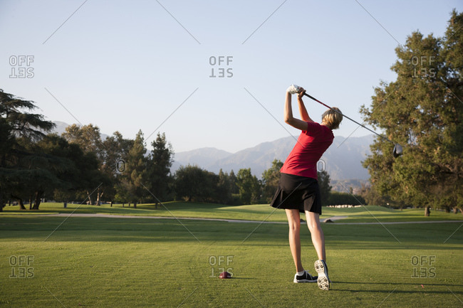 A woman swings at a ball on a golf course