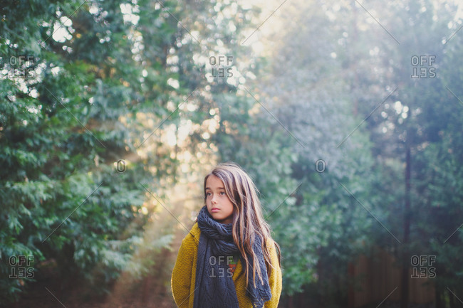 A little girl in a scarf stands in woods
