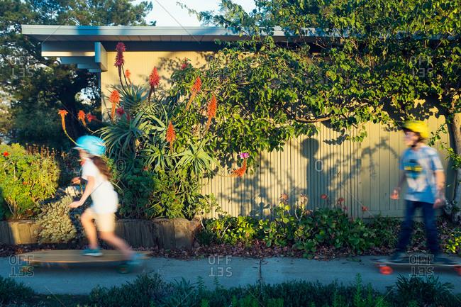 Kids skateboard down a sidewalk
