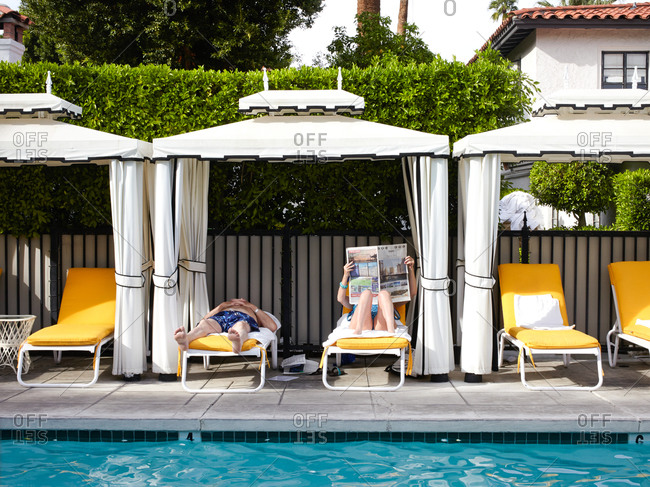 Palm Springs, California - April 15, 2015: Couple relaxing in a poolside cabana in Palm Springs, California