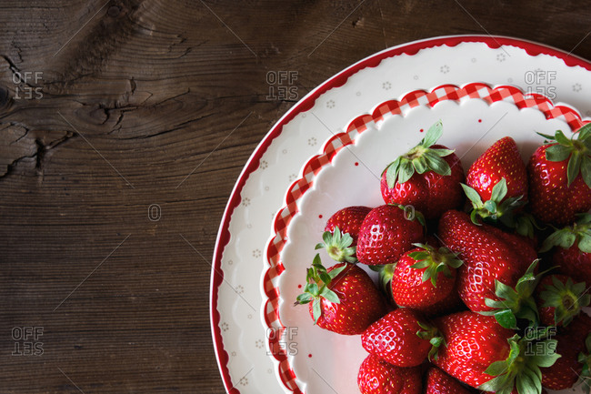 Fresh strawberries on a red and white plate on wooden table