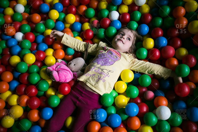 A little girl lies in a ball pit
