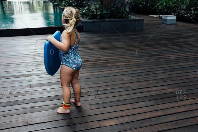 Toddler girl holding kickboard on deck next to pool