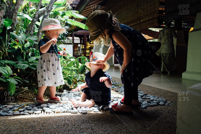 Three young children wearing hats and dresses playing on rocks in an atrium
