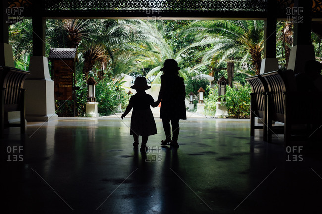 Two young children holding hands in atrium of resort hotel