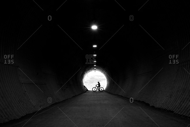 Boy on bike at the end of a tunnel, backlit