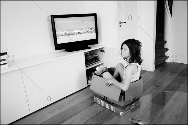 Young boy sitting in a box watching television