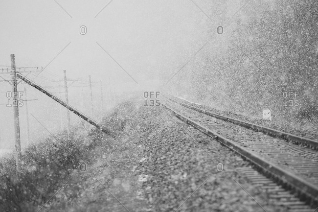 Snow falls on railroad tracks