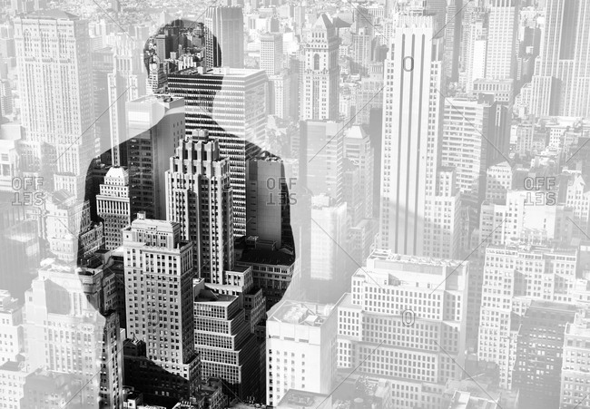 Double exposure of a businessman looking out window over Manhattan, New York